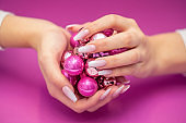 Baby boomer Nails holding small Christmas baubles on pink Background