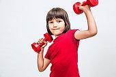 fun child enjoying raising hands with dumbbells expressing proud success