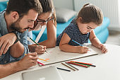 Father and mother teach daughter to draw.