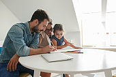 Father and mother teach daughter to draw.They sitting in living room.