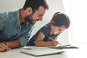 Father teach his daughter to draw.