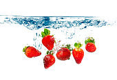 Group of Ripe Strawberries splashing into fresh water on white background