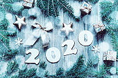 New Year 2020 background -2020 figures, Christmas toys, blue fir tree branches and snowflakes. New Year 2020 still life