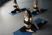 High angle view of three slim women practicing pigeon pose on blue exercise mats during group yoga class, yoga teacher on foreground