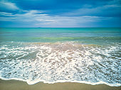 Idyllic beach with clear sand and white waves lapping shore