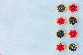Blueberry and Raspberry Tartlets on Blue Concrete Background