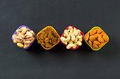 Healthy Mix Dry Fruits and Nuts on dark background. Almonds, Pistachio, Cashews, Raisins
