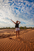 Woman standing barefoot on the dune in the desert