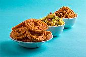 Indian Snack : Chakli, chakali or Murukku and Besan (Gram flour) Sev and chivada or chiwada on blue background. Diwali Food