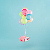 Colorful balloons with pink house flies in the blue sky.