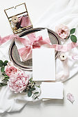 Feminine vertical wedding, birthday mock-up scene. Blank paper greeting cards, eucalyptus, pink roses, peony flowers on white table background.Golden glass box with silk ribbons. Flat lay, top view