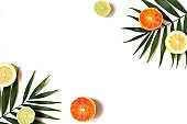 Exotic composition of fresh lemons, red oranges, lime fruit and lush green palm leaves isolated on white table background. Tropical summer vacation concept. Flat lay, top view. Decorative frame.