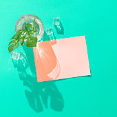 Tropical cocktail with ice cubes and pink paper card note on vivid blue background.