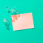 Ice cubes and pink paper card note on vivid blue background.