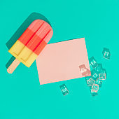 Ice cream popsicle with ice cubes and pink paper card note on vivid blue background. \