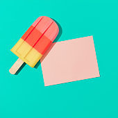 Ice cream popsicle with pink paper card note on vivid blue background.
