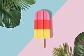 Ice cream popsicle in pastel pink on paper duotone background with tropical palm leaves.