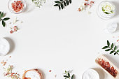 Styled beauty frame, web banner. Skin cream, tonicum bottle, dry flowers, leaves, rose and Himalayan salt. White table background. Organic cosmetics, spa concept. Empty space, flat lay, top view.