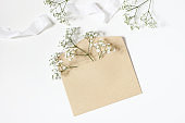 Styled stock photo. Feminine wedding desktop mockup with baby's breath Gypsophila flowers, satin ribbon and blank craft paper envelope mockup on white table background. Top view, flat lay.