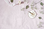 Styled stock photo. Feminine wedding desktop scene. Baby's breath Gypsophila flowers, dry green eucalyptus leaves, satin ribbon, golden scissors on pink linen background. Empty space. Top view.