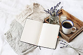 French summer still life. Feminine lifestyle composition. Cup of coffee, lavender flowers bouquet, candle on wooden tray. Linen shirt nad trousers on bed. Blank notebook mockup scene. Top view.