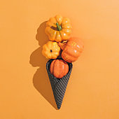 Icecream made with black ice-cream cone and pumpkins on orange background.