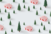Trendy Christmas pattern made with pink houses and pine trees.