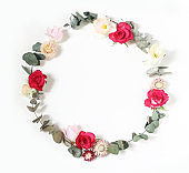 Spring, Easter feminine styled scene, floral composition. Round frame wreath made of pink roses, tulips, daffodils, everlasting flowers and eucalyptus branches. White background. Flat lay, top view.