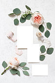 Wedding stationery, birthday mock-up scene. Blank greeting cards, silk ribbons, eucalyptus leaves and blush pink English roses flowers. White concrete table background. Flat lay, top view,vertical.