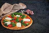 Italian pizza with Mozzarella cheese, tomatoes, broccoli, Spices and fresh basil. Pizza and kitchen napkin near, on black stone background