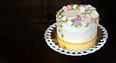 SWEET FLORAL BUTTERCREAM BIRTHDAY, ANNIVERSARY OR MOTHERS DAY CAKE AGAINST DARK WOODEN BACKGROUND