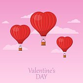Three red heart air balloons flying in the pink sky with clouds. Saint Valentine's day greeting card. Hot air balloon shape of a heart with basket.