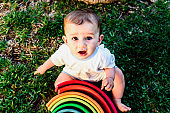 6 month old baby using to play a wooden rainbow puzzle, improving his skills, view from above.