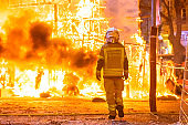 Firefighter with his protective suit working controlling the burning of a Falla during the Valencian fiestas.