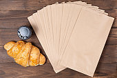 croissant in paper bag on wooden background with paper disposable cup of coffee. concept of continental breakfast and eco packaging