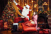 Santa Claus with little cute amazed girl in pajama packing gifts