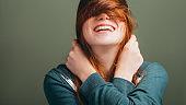 female expressing joy toothy smile messing hair