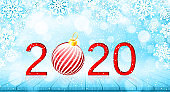 Merry Christmas and Happy New Year 2020 banner. Holiday vector illustration with paper snowflakes background, red number and christmas ball on wooden table