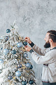 winter holidays guy decorating fir tree blue ball