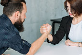 gender equality leadership man woman armwrestling