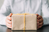 goods delivery service beige gift box man hands