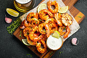 Grilled shrimps or prawns served with lime, garlic and white sauce on a dark concrete background. Seafood. Top view. Flat lay