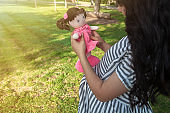 pregnant girl walks in the park with a doll