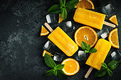 Bright popsicle made of oranges on a dark concrete background. Sweet summer treat. Top view with copy space. Flat lay