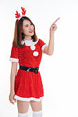 Portrait of a charming beautiful woman in red santa claus costume pointing up showing copyspace. Isolated on white background.