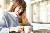 Young asian woman beautiful smile with friends enjoying coffee together in a coffee shop,Smiling woman in a good mood with cup of coffee sitting in cafe while relaxing in cafe during free time
