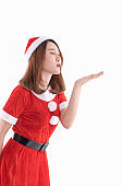 Portrait of beautiful smiling christmas santa woman in red santa claus costume blowing a kiss against isolated over white background