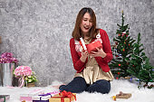 Happy young woman christmas hat opening a christmas present box at home. Holidays New Year and Christmas.