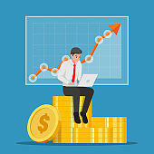 Businessman sitting on coin stack with laptop and stock market graph