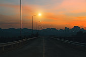 Mountain highway. Amazing landscape with rocks, sunset sky and mystic asphalt road going to horizon at the evening. Vintage toning. Summer adventure background. Travel by car.